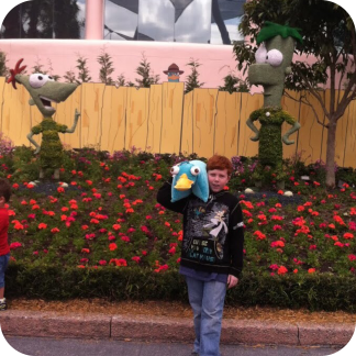 Big J with his Perry the Platypus pillow by some Phineas and Ferb topiary